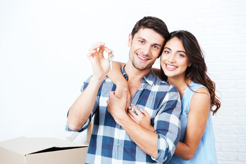 bigstock-Young-smiling-couple-showing-k-133535282-min