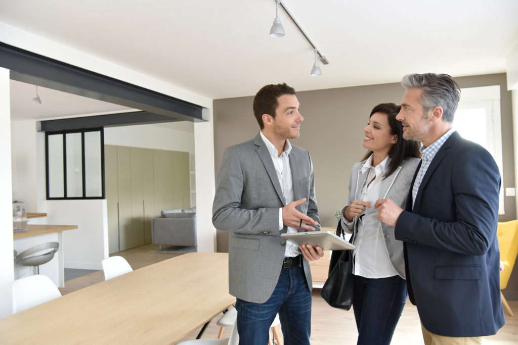Mature couple with real-estate agent visiting new house